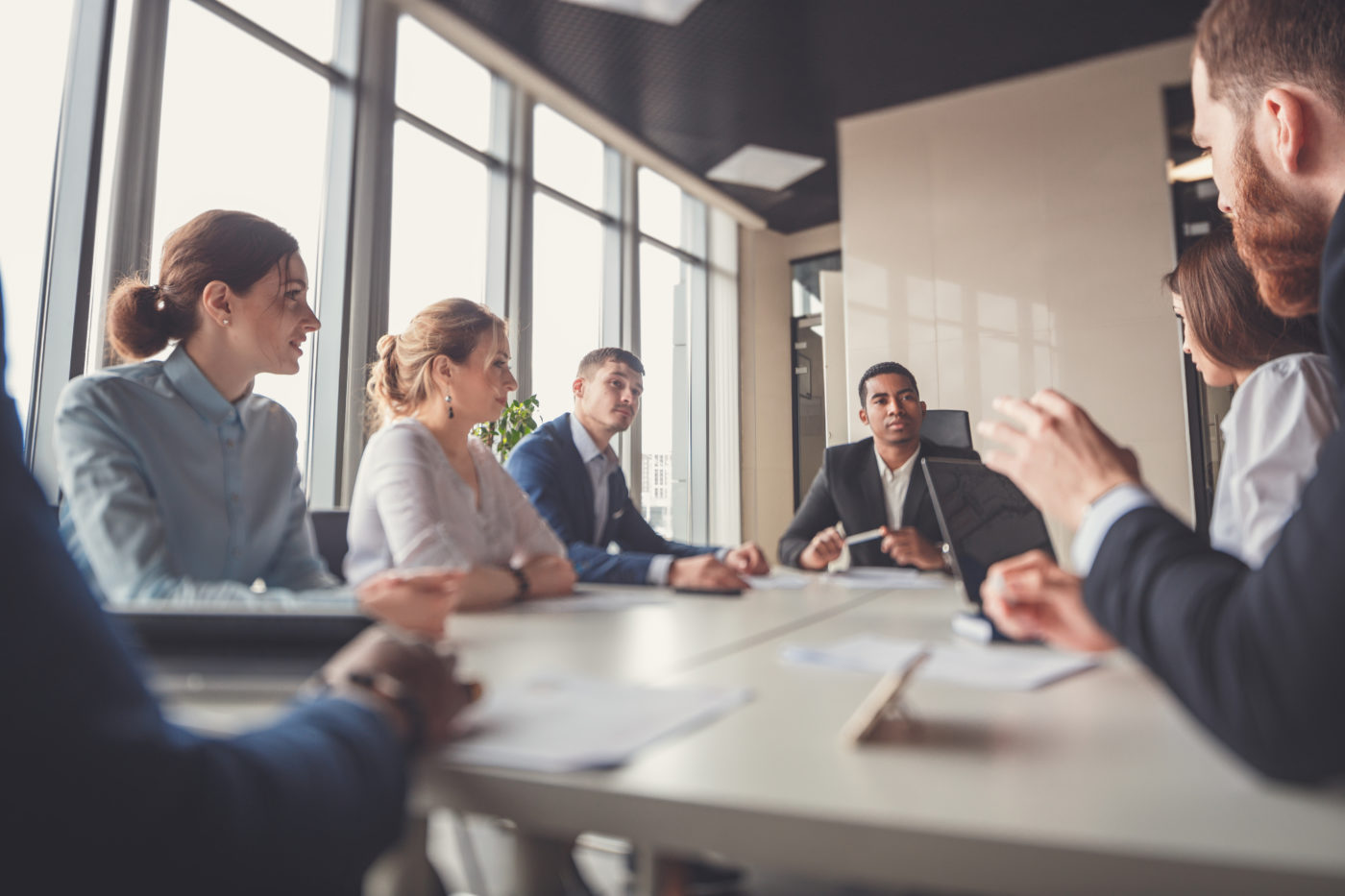 Group of executives have a meeting around a table talking about finding a facilitator